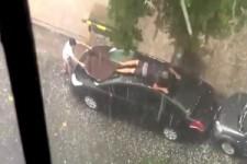 Ein Mann verteidigt sein Auto vor Hagel